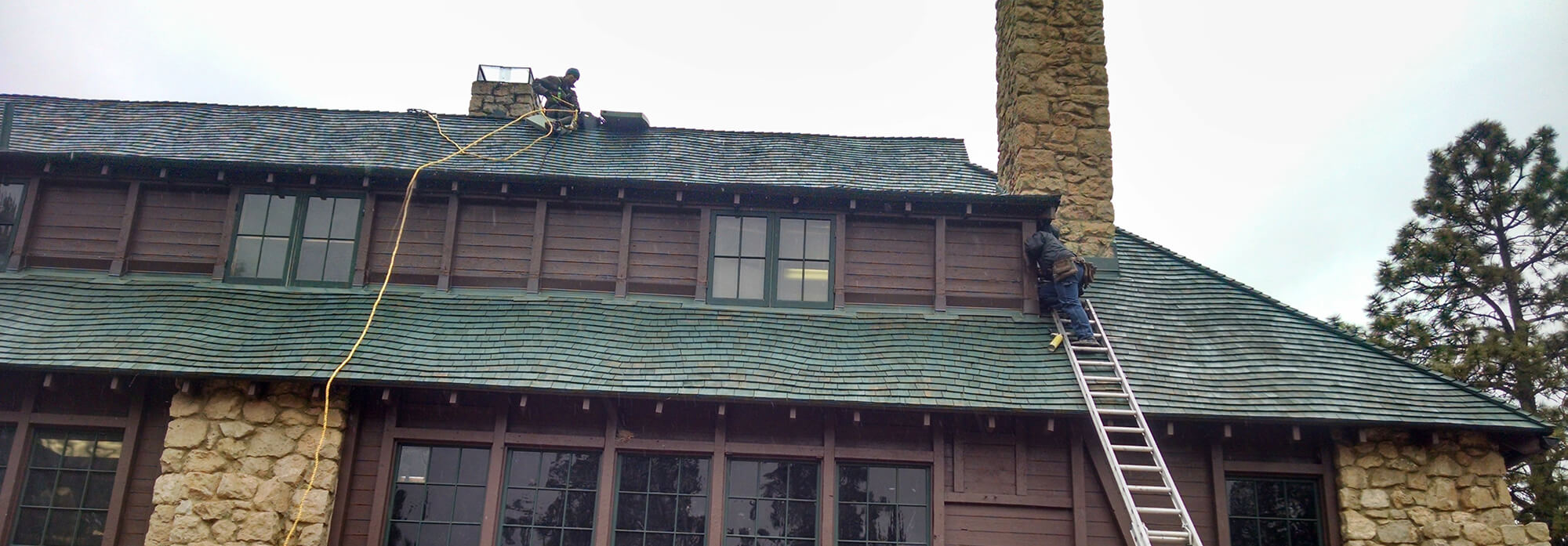 two technicians seal up bat entry on a roof
